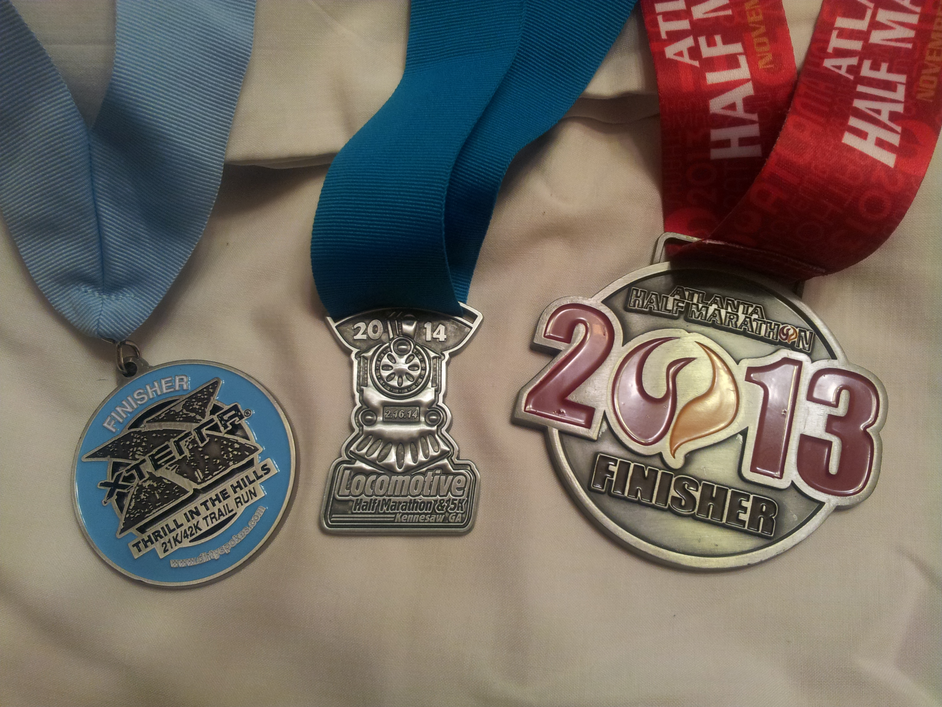 The finisher medals of each of my three half marathons, completed 86 days apart, two within six days.  From the right Thanksgiving 2013 Atlanta Half,  February 16 2014 Locomotive Half Marathon, and February 24 2014 Xterra Thrill In the Hills 21k and 42k.