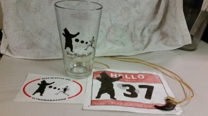 My loot from the Bear Blaster 50k, a pint glass, my race bib and a bear claw finisher award.